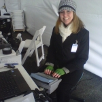 Image of a captioner with her stenography machine and a coat, hat, and scarf