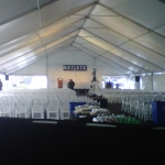 Image of a tent with white chairs set up for a conference