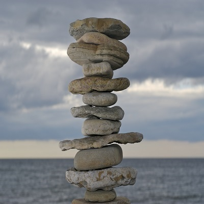 Image of different size rocks stacked on top of one another with a cloudy sky and sea background