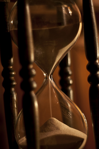 Image of an hourglass with sand flowing through it
